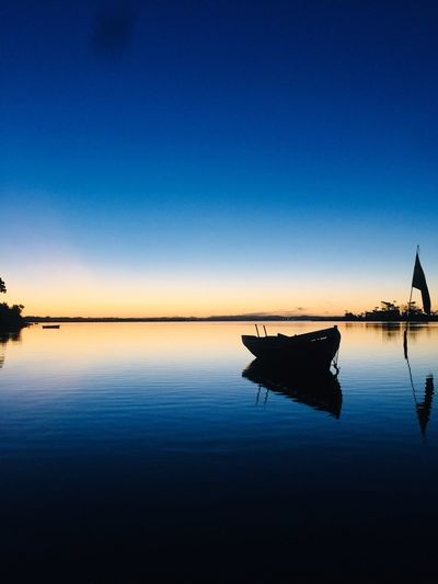 Silhouette boat moored in lake against clear blue sky during sunset