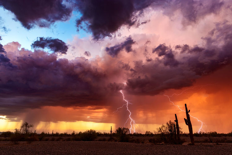 Scenic view of landscape against storm clouds against sky during sunset