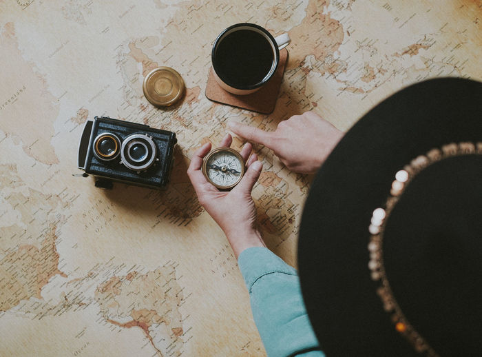 One Person Coffee Indoors  Lifestyles Coffee - Drink Holding Coffee Cup Cup High Angle View Mug Wanderlust Travel Destinations Travel Planning Vintage Camera Woman Compass Adventure