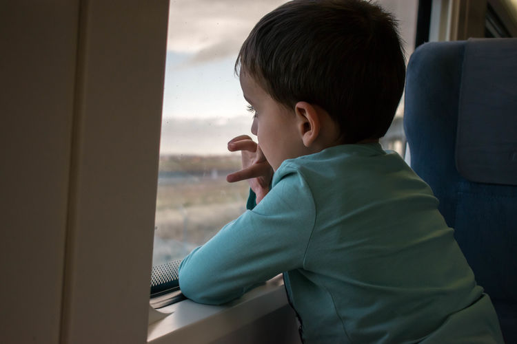 Side view of boy looking through airplane window
