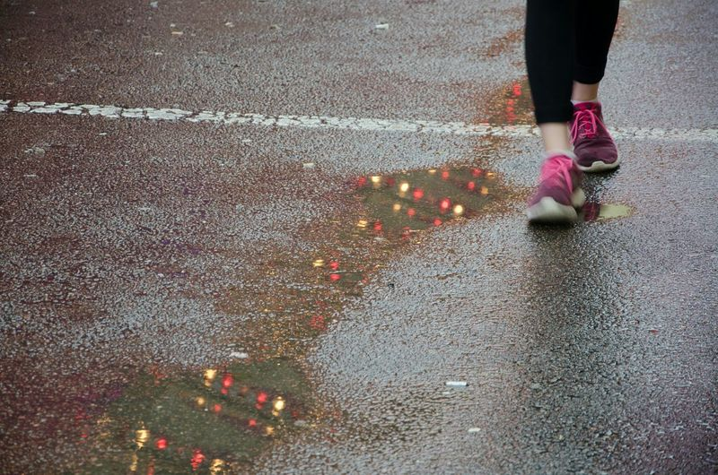 Low section of woman walking on wet street during monsoon
