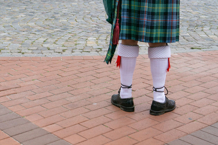 Low section of person in traditional clothing standing on footpath