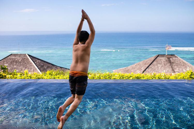 Full length of shirtless boy jumping in swimming pool against sea