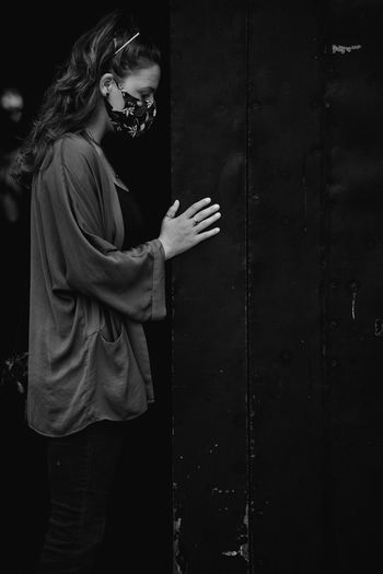 Side view of young woman wearing mask standing against door