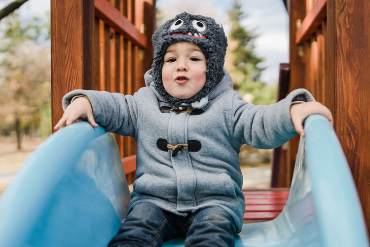 Portrait of cute baby boy sitting on slide at playground