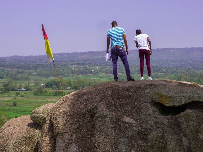 Rear view of couple standing on rock against clear sky
