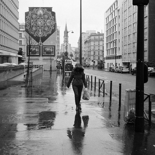 Full length of woman walking on wet city street against sky