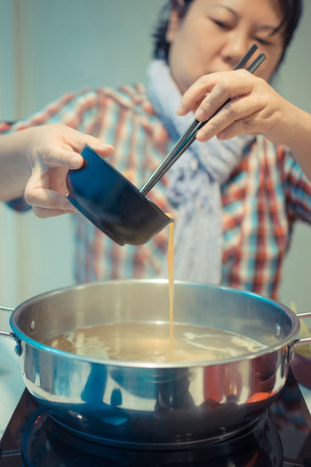 Woman Pouring Liquid In Container At Kitchen