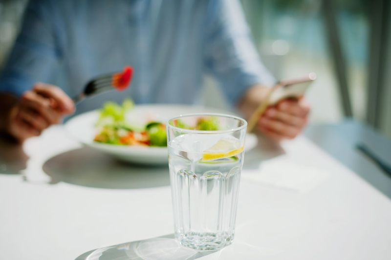 young guy eating a salad Food And Drink Glass One Person Holding Adult Drinking Glass Table Food Focus On Foreground Freshness Refreshment Women Drink Midsection Household Equipment Indoors  Real People Healthy Eating Human Hand Hand