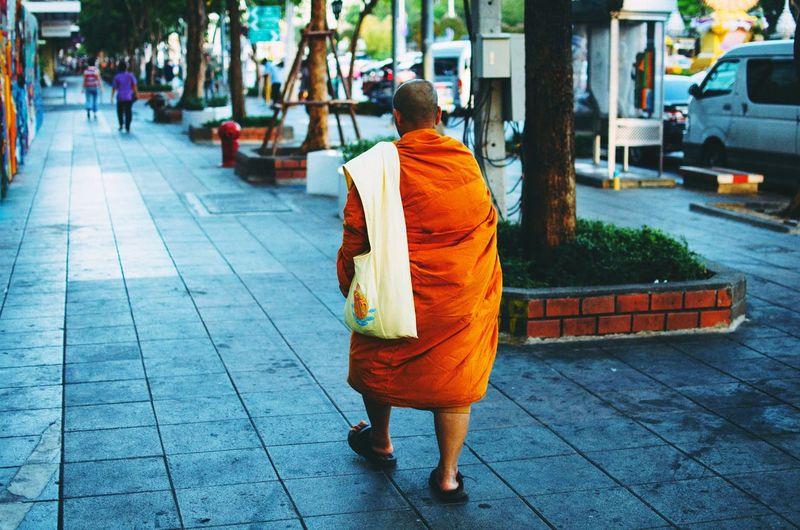 Man In Orange Toga On Street