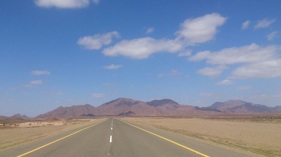 Empty Road With Mountains In Background