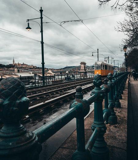Bridge over railroad tracks in city against sky