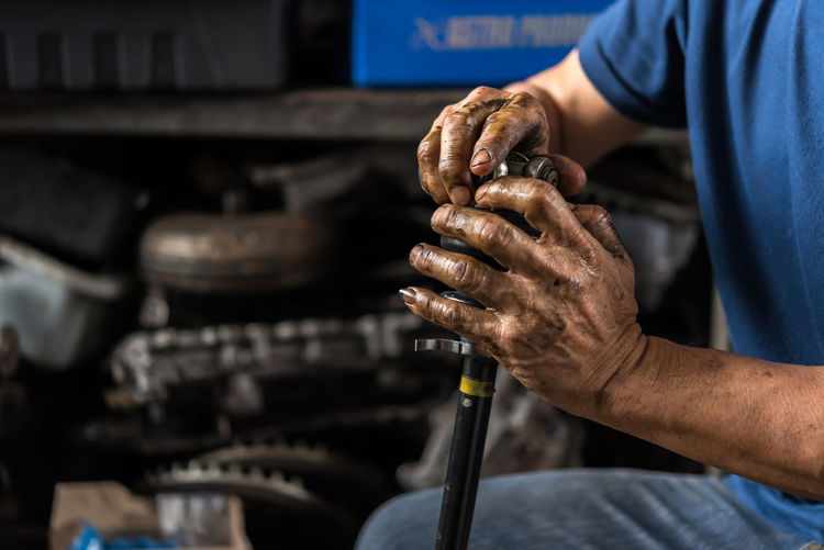 Occupation Working One Person Holding Men Hand Indoors  Auto Repair Shop Mechanic Human Hand Real People Skill  Technician Business Repairing Auto Mechanic Midsection Adult Repair Shop