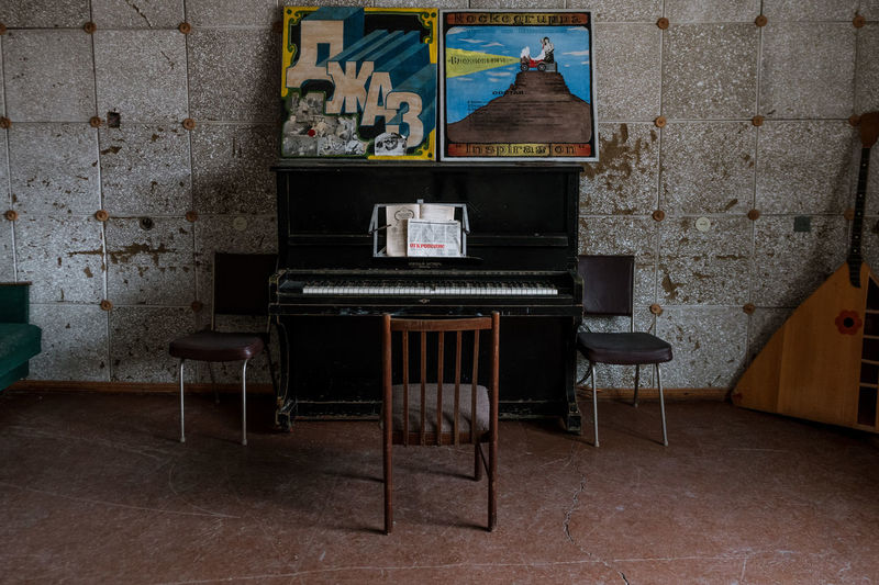 Empty chairs and table against wall in old house