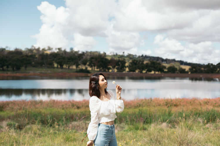 Full length of woman standing by lake against sky