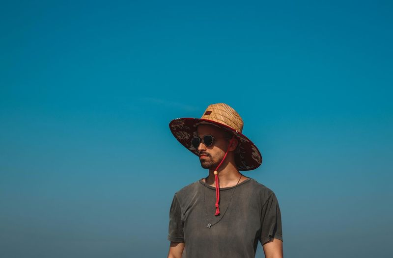 Man wearing hat while standing against clear blue sky