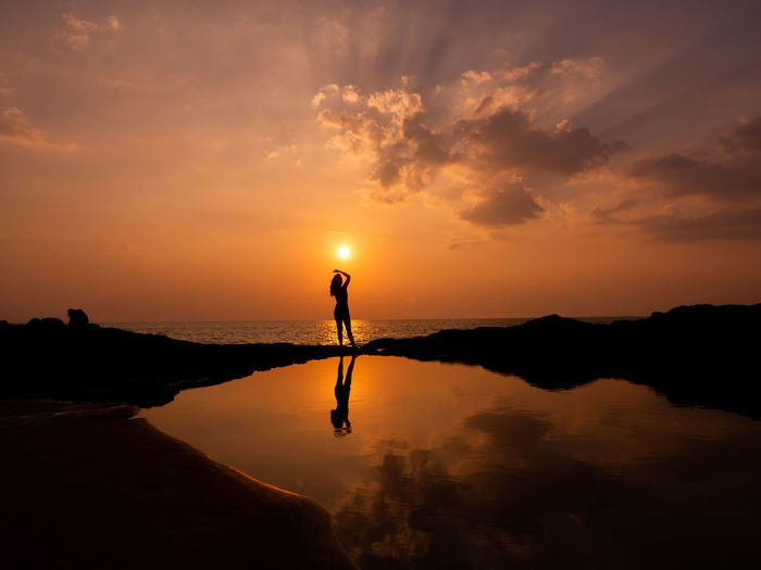 Beautiful silhouette woman at heavenly sunset at sea. sunlight sky at the sunset at the horizon