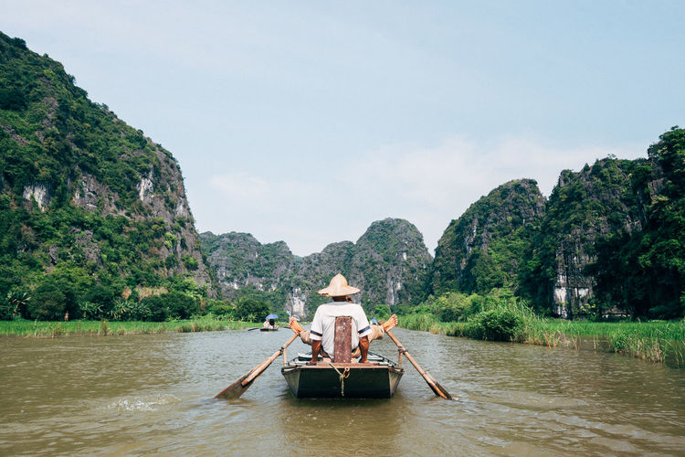 Rear View Of Man Boating In River Against Sky