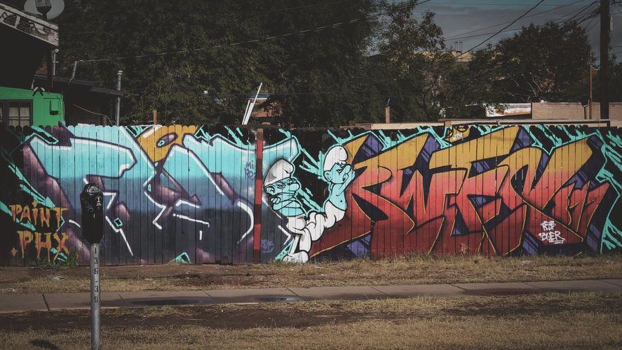 Graffiti on wall by trees