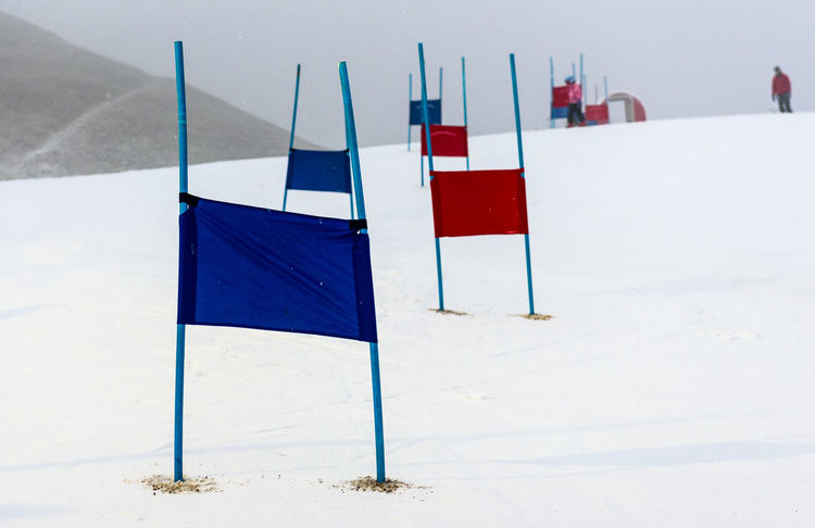 Children skiing slalom racing track with blue and red gates. Small ski race gates on a pole with children skiing in the background. Children Gates Skiing Skiing ❄ Slovenia Child Flag Outdoors Pole Race Racing Track Shildren Ski Racing Slalom Track Winter
