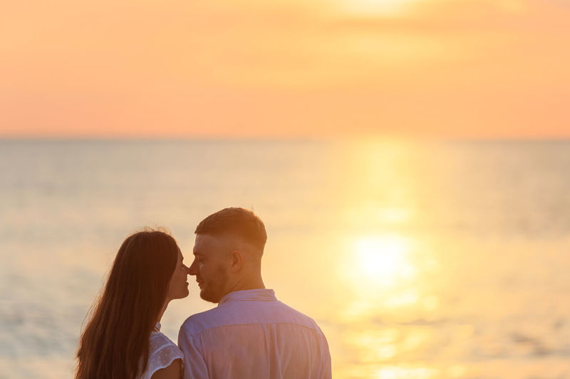 Couple Romancing At Beach Against Sky During Sunset