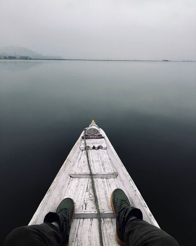 Low section of man sitting in rowboat in lake