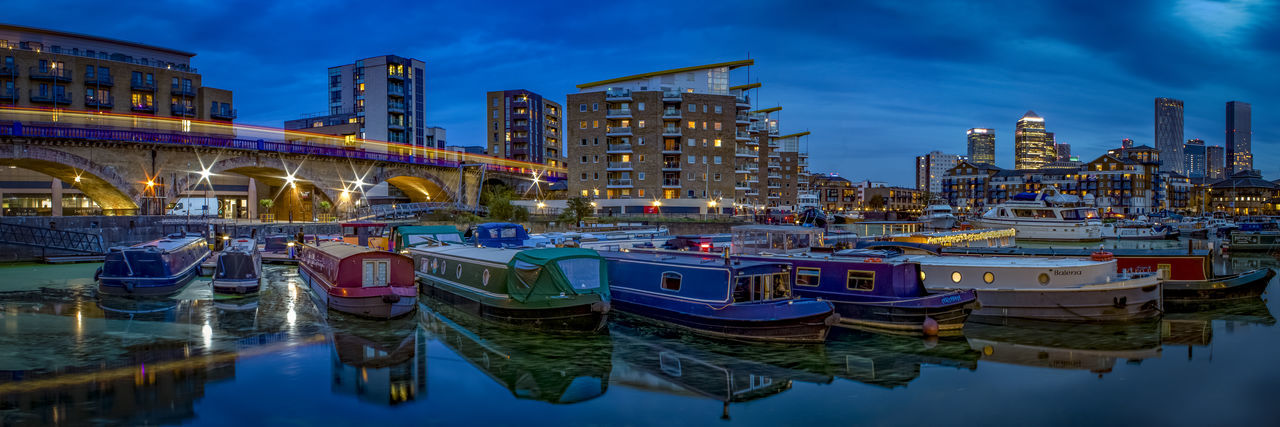 Boats moored in river by illuminated buildings against sky at dusk