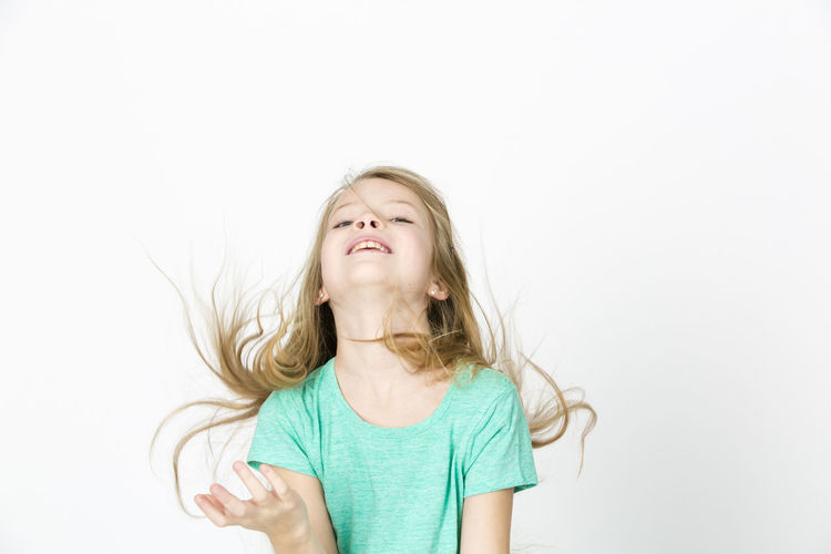 Playful Girl Tossing Hair While Standing Against White Background