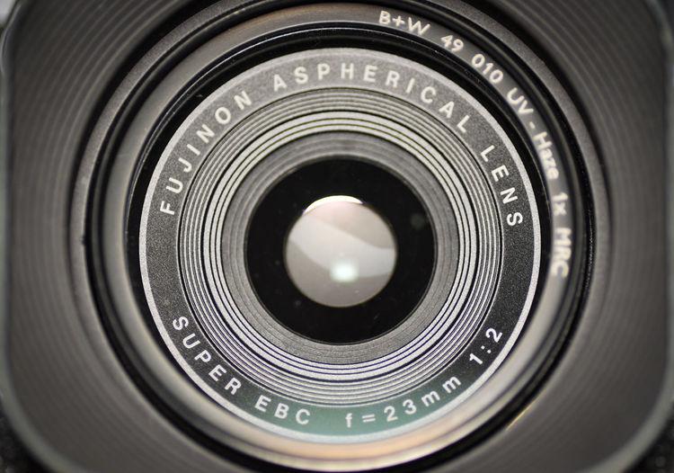 Close up shot of a camera lens fujinon f=23mm 1:2 B+W 010 Filter FUJIFILM X100S Fujinon 23mm F2 Aspherical Lens Black Color Camera Camera - Photographic Equipment Close-up Digital Camera Fujinon Lens Lens - Optical Instrument No People Photographic Equipment Photography Themes Super EBC Technology