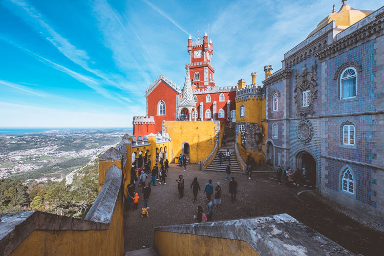 The colourful Pena Palace of Sintra, Portual. Architecture Built Structure Building Exterior Sky Water Nature City Building Travel Destinations Travel History Incidental People Cloud - Sky The Past Tourism Day Sea Panoramic Outdoors Palace Castle Sintra Colourful Wide Angle