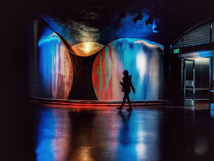 Silhouette people walking on illuminated lights