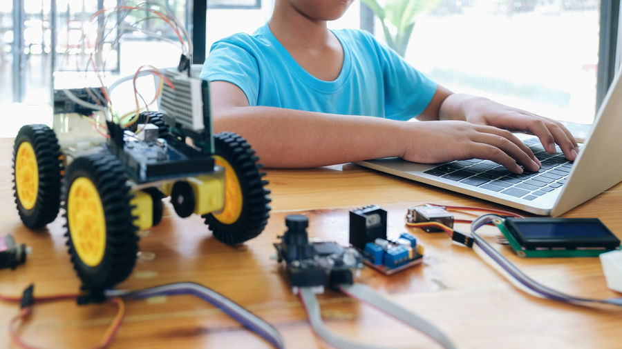 Midsection of boy using laptop by toy on table