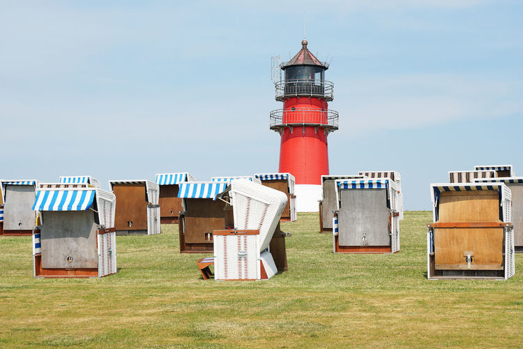 Hooded beach chairs on field and lighthouse against sky