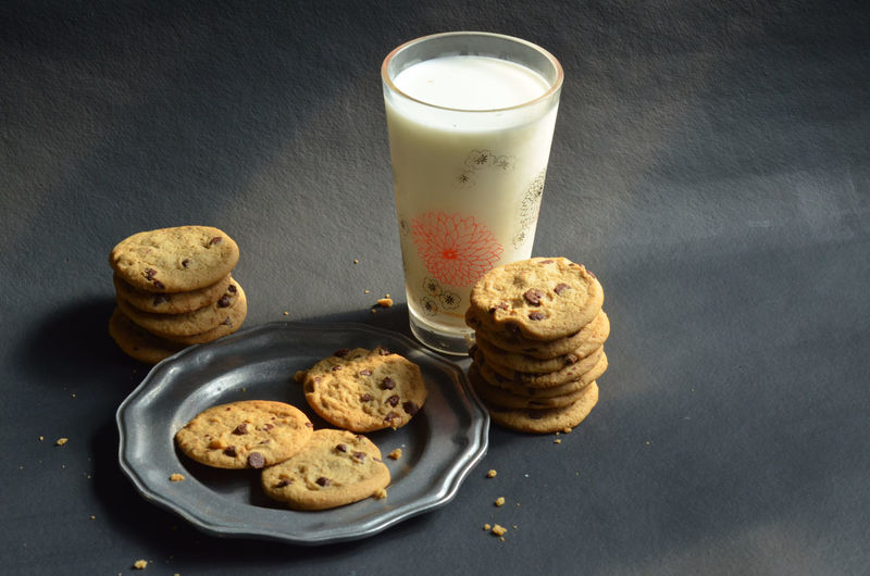 High angle view of chocolate chip cookies with milk