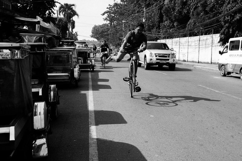 Transportation Bicycle Land Vehicle Mode Of Transport Street Car Road Tree Day Shadow Outdoors Sunlight Real People City One Person Sky Adult People Adults Only Monochrome The Week On EyeEm Bloomberg Eyeem Philippines EyeEmNewHere EyeEm Best Shots Visual Creativity