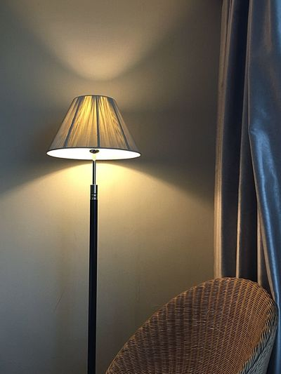 Illuminated lamp by chair at home