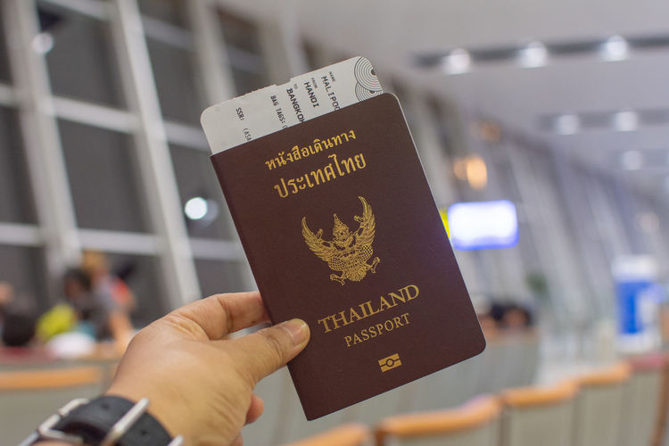 Human Hand Hand Text Passport Communication Real People Human Body Part Travel Holding Focus On Foreground One Person Western Script Transportation Unrecognizable Person Journey Tourism Personal Perspective Airport Incidental People Finger Airplane Ticket Government Arrival