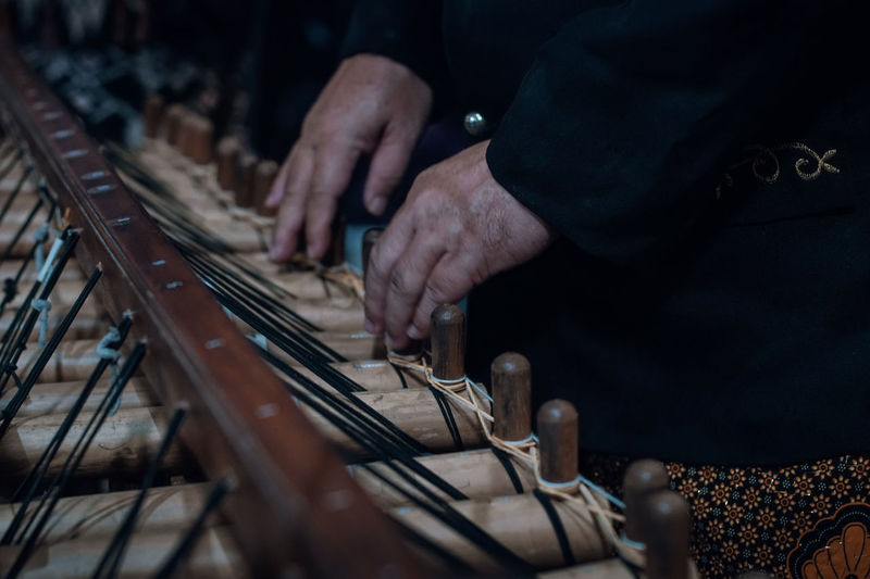 Midsection of man playing angklung