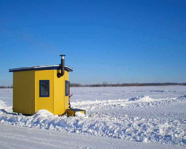 Yellow cabin on snow covered landscape against clear blue sky