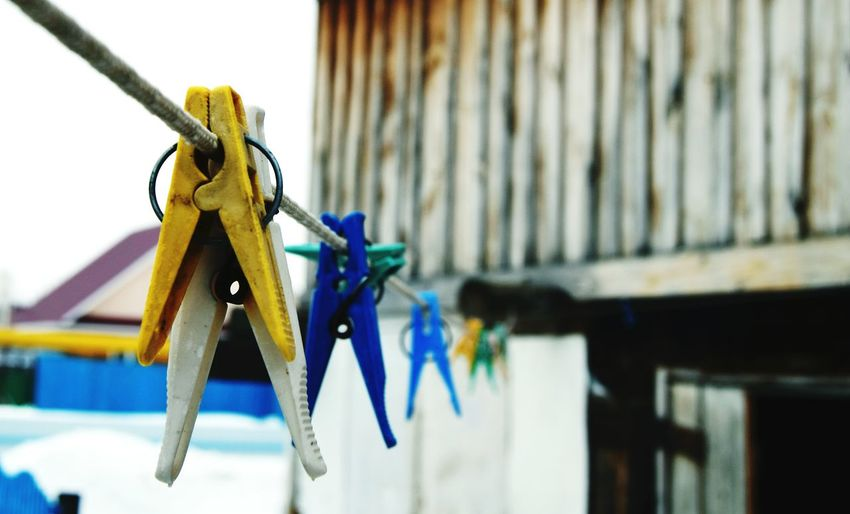 Close-Up Of Clothes Pegs Hanging On Clothesline