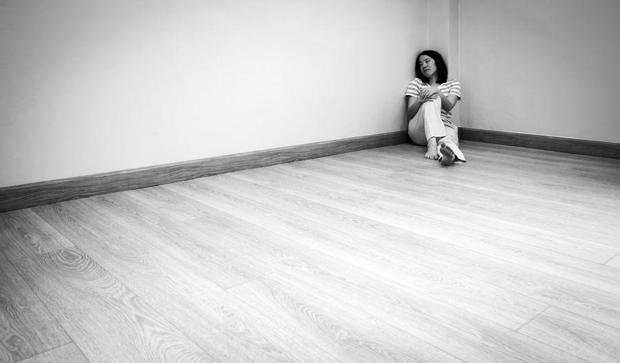 Full length of woman sitting on hardwood floor against wall