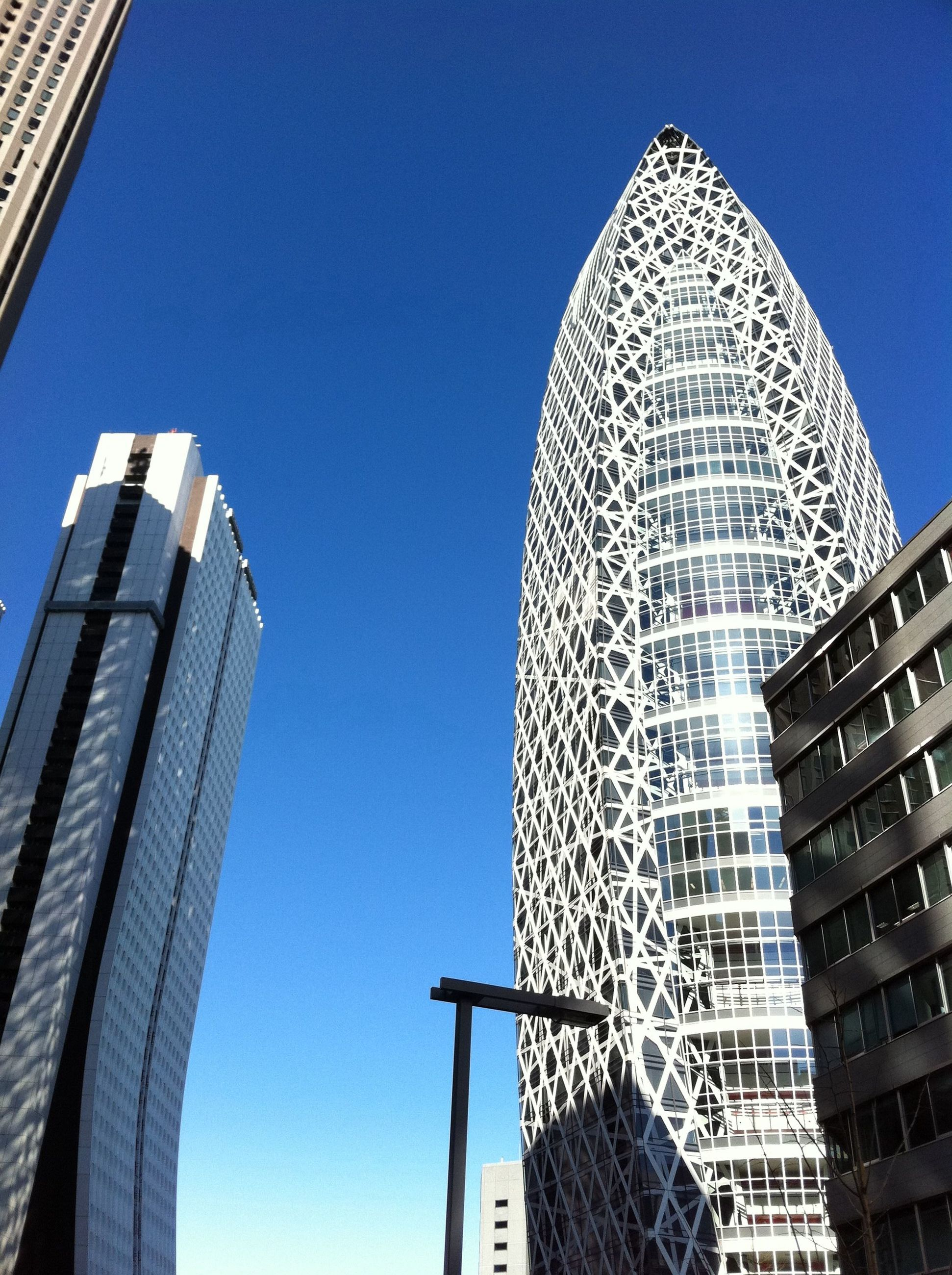 low angle view, architecture, building exterior, built structure, modern, blue, clear sky, tall - high, skyscraper, tower, office building, city, sky, famous place, travel destinations, building, capital cities, directly below, day, no people