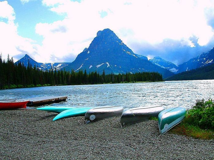 Everybody deserves a rest. The canoes are put down at the lake shore of Two Medicine Lake for the night.. Glacier National Park Montana Montana Outdoor Activity The Great Outdoors - 2018 EyeEm Awards Tranquility Two Medicine Lake, Montana Beauty In Nature Blue Canoes Canoes On Lake Dusk Glacier National Park Lakeshore Mountain Mountain Range Nautical Vessel Outdoor Activities Outdoor Photography Outdoor Pursuit Relaxation Tranquil Scene Tranquility Transportation Two Medicine Lake Water
