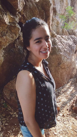 Portrait of smiling young woman standing against rock formations