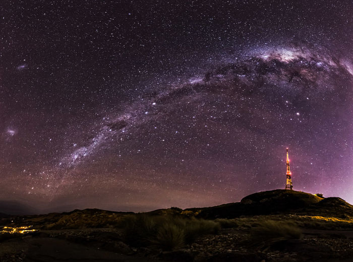 Low Angle View Of Illuminated Communications Tower Against Milky Way