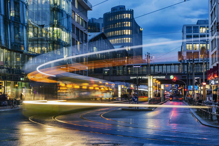 Shopping Area of Friedrichstrasse at Dusk with Light Trails of Tramway and Railway Station in Background Berlin Germany 🇩🇪 Deutschland Color Image Horizontal No People Outdoors Illuminated Transportation Architecture Built Structure Motion Blurred Motion Road Building Exterior City Street Long Exposure Mode Of Transportation Speed Dusk Friedrichstrasse Light Trail Tramway Tram Traffic