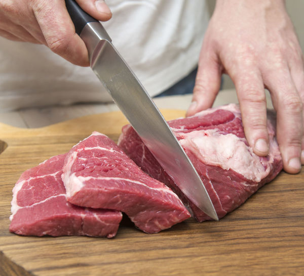 Midsection Of Man Cutting Meat On Board