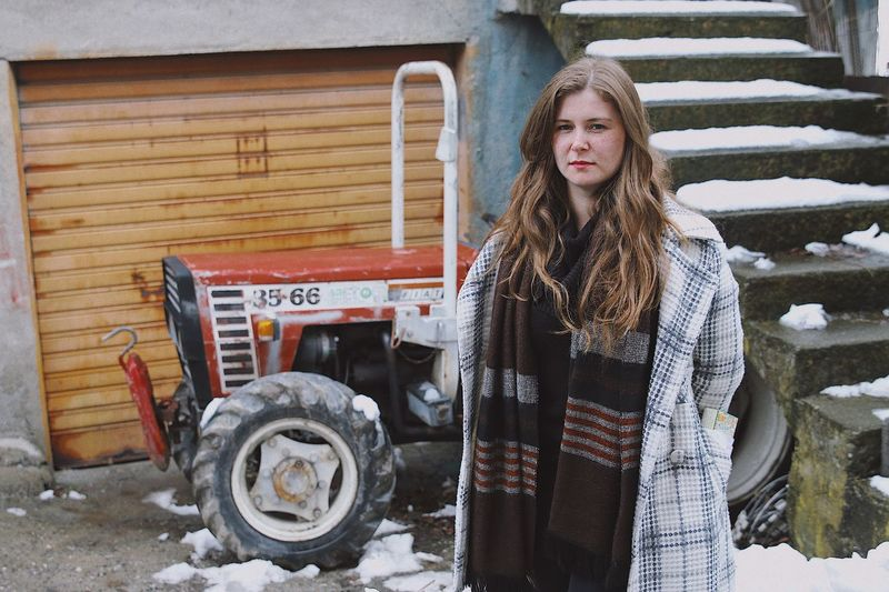 Portrait of woman standing against snow on tractor and staircase