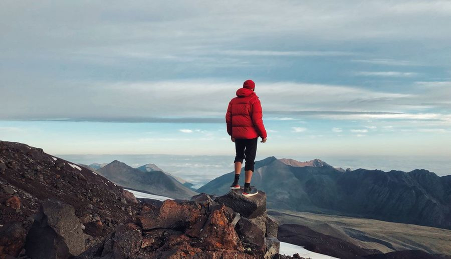Man standing on rock looking at mountains against sky