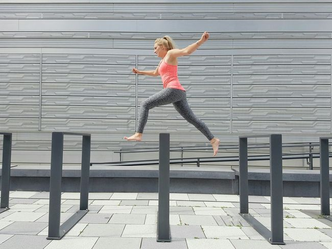 Jump Modern Architecture Facades Wall Silver  Shades Of Grey Woman Jumping Running Building Exterior Young Adult Pedestrian Walkway Outdoors Doing Sport The Color Of Sport Hurdles Race Athletic Healthy Lifestyle Sportswear Pink Top Summer In The City Embrace Urban Life Streetphotography Urban Geometry Stories From The City